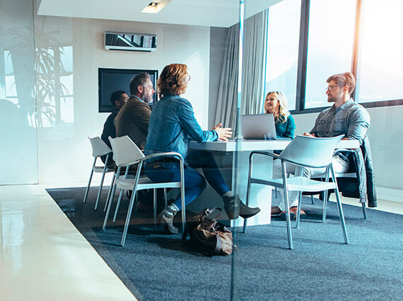 Group of people sitting around a table in a conference room