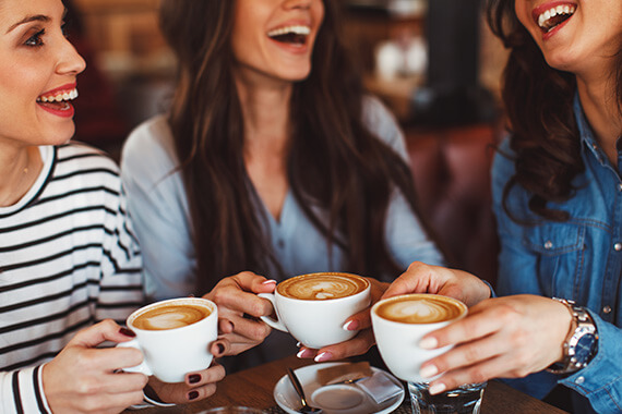 A group of females laughing while enjoying lattes at a cafe
