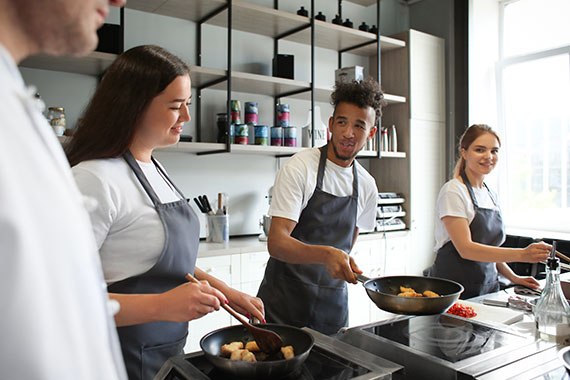 People in aprons learning to cook in a test kitchen