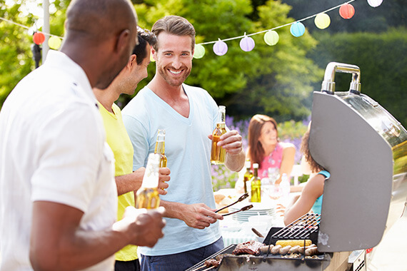 Smiling males standing in front of a grill at a backyard BBQ
