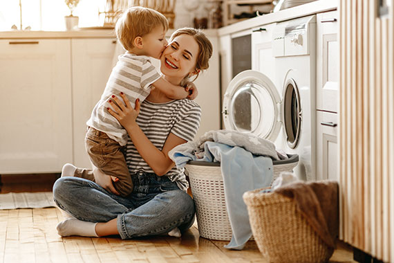 Woman hugs child while doing laundry