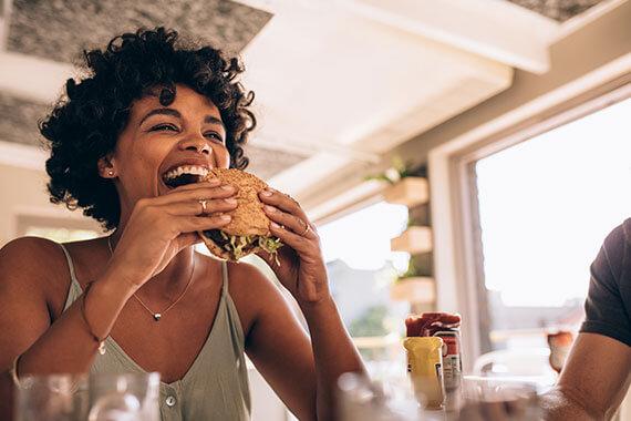 Woman laughing as she eats a hamburger