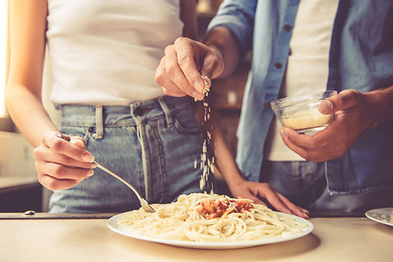 Man sprinkling cheese onto a plate of pasta
