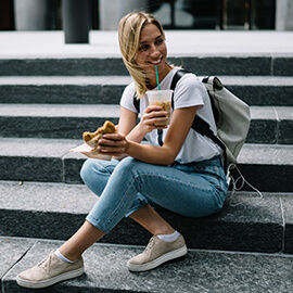 Woman sitting on steps eating fast food