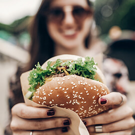 Woman smiling holding a burger