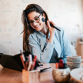 Woman smiling while applying makeup
