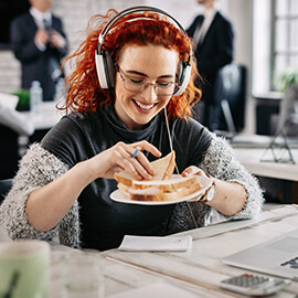 Woman with headphones eating a sandwich at her desk