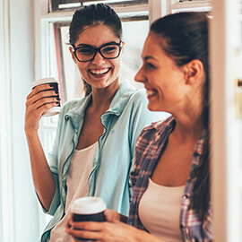 Two woman laughing while holding coffees