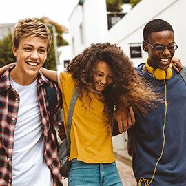 Three teens walking together smiling