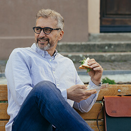 Man sitting on a bench eating a sandwich