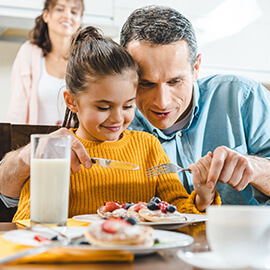 Father helping daughter cut breakfast